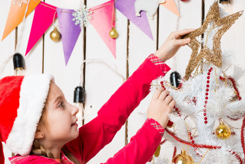 Child placing star on tree
