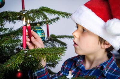 Boy lighting candle on tree