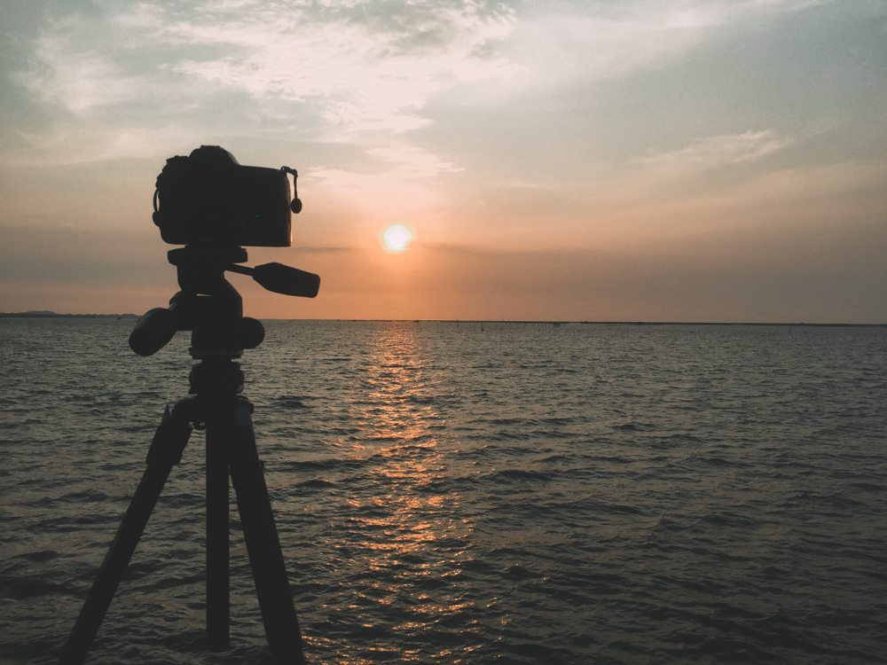 camera and tripod set up on the beach to capture the sunset