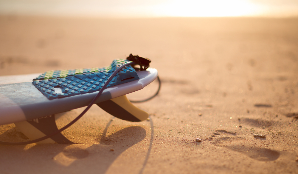 surf board on beach shores at sunset