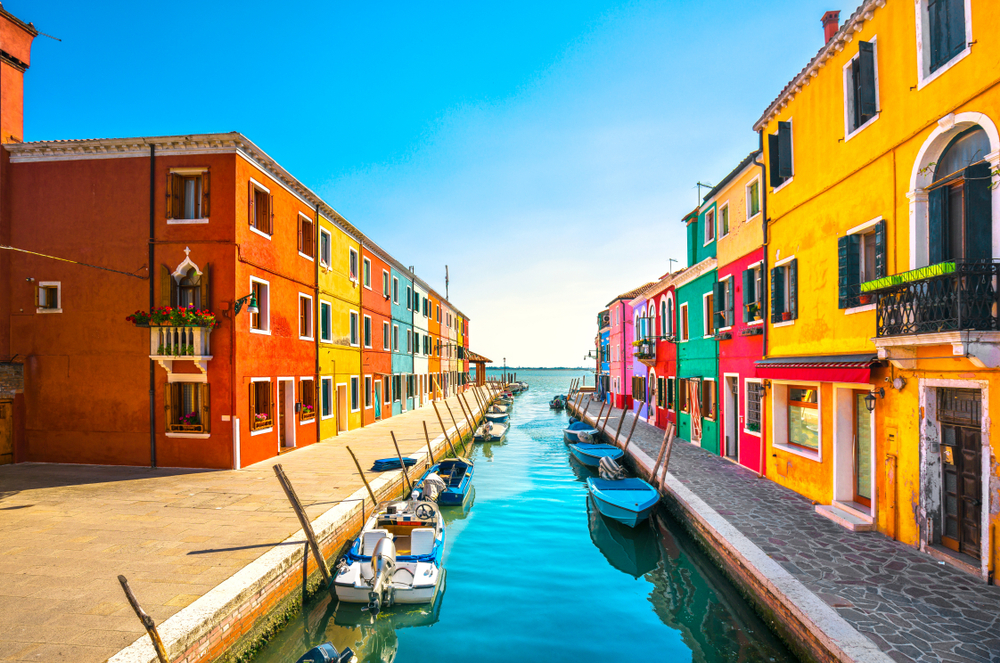 coloured houses and boats on the water in venice, italy