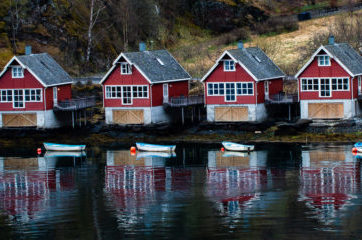 3 Norwegian boathouses with reflections in the water