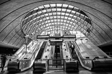 Black and white image of escalators in train station