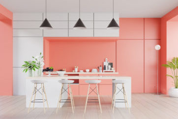 Coral and white coloured kitchen with island and bar stools