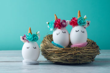 unicorn decorated eggs sat in nest