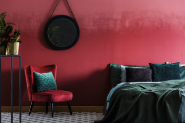dark red and green bedroom interiors with hanging mirror and indoor plants
