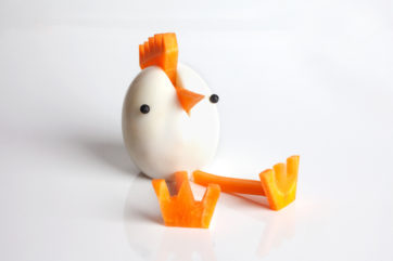 Boiled egg styled into a chick with carrot legs
