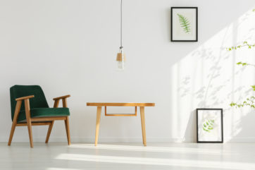 Light space with frames, natural wooden furniture and low-hanging light