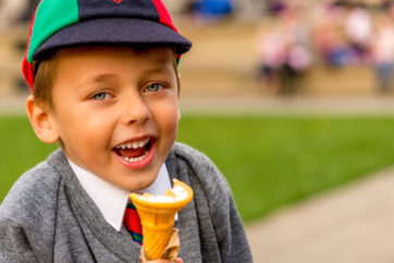 Close-up of a laughing uniformed schoolboy in a grey pullover, white shirt, tie and striped cap eating an ice-cream